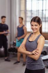 frau steht lächelnd mit verschränkten armen im fitnessstudio