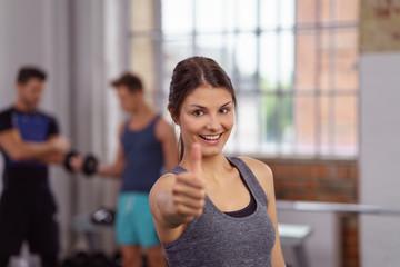 glückliche frau im fitness-studio zeigt daumen hoch