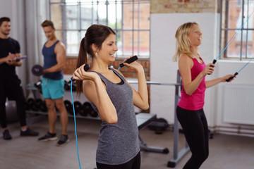 lachende frauen beim seilspringen im fitnessstudio