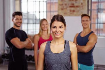 lächelnde junge frau im fitnessstudio mit freunden hinter ihr
