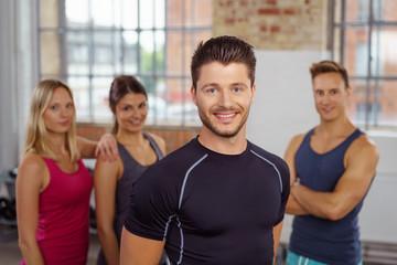 lächelnder mann im fitnesstudio mit team im hintergrund