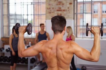 sportlicher mann trainiert mit gewichten im fitness-studio