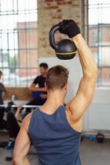 mann trainiert mit einem gewicht im sportstudio