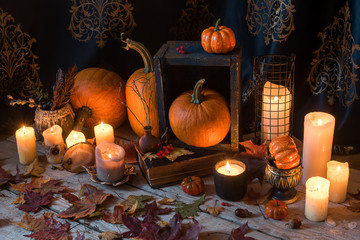 Pumpkins,candles, autumn leaves on rustic wooden table