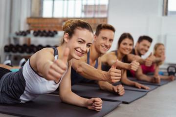 teilnehmer beim fitnesskurs zeigen daumen hoch