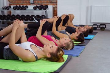 sportler dehnen ein bein beim fitness-kurs