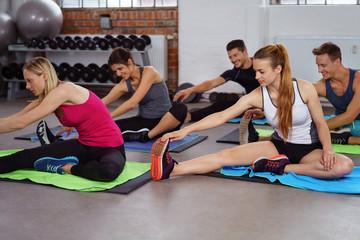 männer und frauen dehnen die beine im fitness-kurs