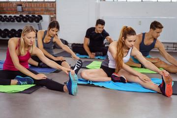 gruppe im fitness-club dehnt die beine
