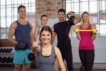frau im fitness-studio zeigt nach vorn und lacht