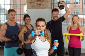 frau im fitness-studio zeigt nach vorne