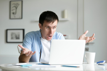 Portrait of a man working at the desk with a laptop, shocked, his hands aside, education,  internet concept photo. Lifestyle