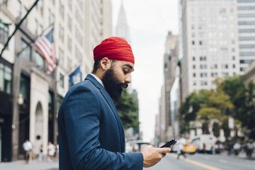 Indian businessman crossing street in Manhattan, looking at smart phone