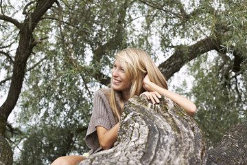 Smiling young woman leaning at a tree trunk