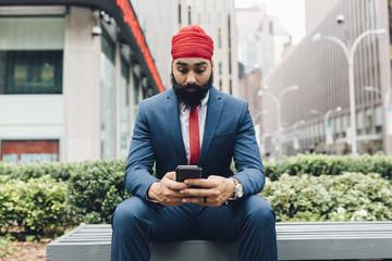 Businessman sitting with smartphone, Manhattan, USA