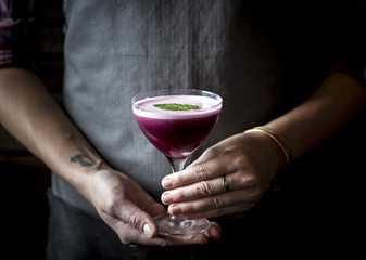 Woman holding blueberry cocktail in coupe glass