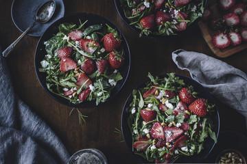 Bowls of strawberry, spinach and arugula salad
