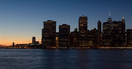Wall Mural - New York City Lower Manhattan skyscrapers from sunset to dusk through nightfall with city lights. Time lapse cityscape view of the Financial District and East River