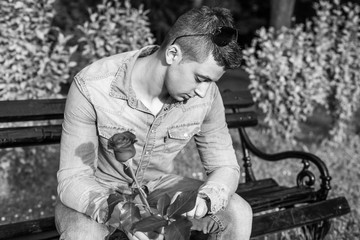young handsome man with red rose on bench
