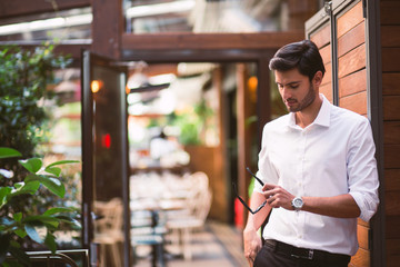 Man in white shirt with sunglasses in hand at cafe