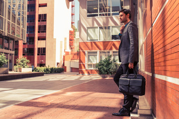 Handsome man in suit with briefcase in the street