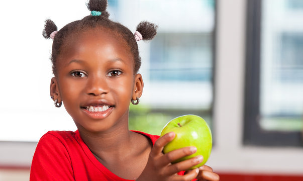 African girl at school with apple in hand