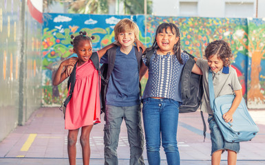 Happy multi ethnic classmates embracing in schoolyard, happiness