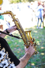 Hands of man playing the saxophone at outdoor