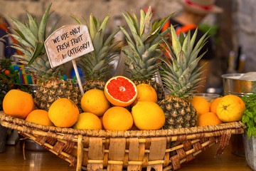 Wicker basket with oranges and pineapples on sale