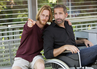 young man showing something to man in wheelchair