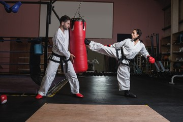 Man and woman practicing karate with punching bag