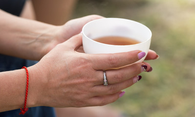 tea in the woman's hand on nature