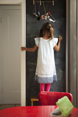 A young girl stands drawing on a chalkboard wall;San francisco california united states of america