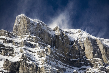 Snow covered mountain peak with blowing snow off the peak and blue sky;Banff alberta canada