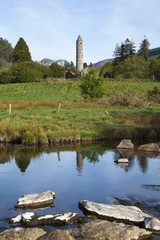 A round tower with the reflection in a tranquil pond in the foreground;Glendalough, county wicklow, ireland