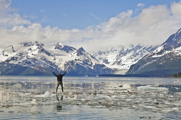 A man basks in the glorious panoramic view of harriman fjord in june with glaciers and mountainous peaks serving as a backdrop;Prince william sound alaska united states of america