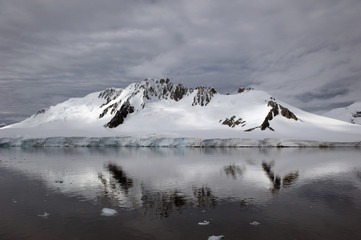 A mountain reflected in the tranquil southern ocean;Antarctica