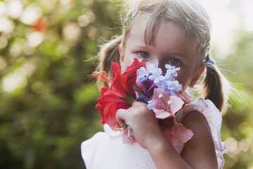A young girl smelling a colourful bouquet of flowers;Torremolinos malaga spain