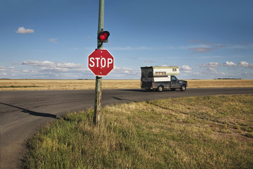 A Stop Sign And Red Light At An Intersection; Saskatchewan, Canada