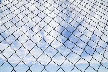 Chain Link Fence And Blue Sky With Cloud; Canada
