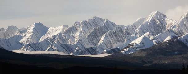 Snow covered mountain range with cloud in valley;Kananaskis alberta canada