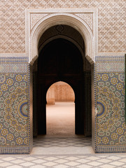 A doorway in a keyhole shape with a colourful tile design on the wall