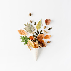 waffle cone with dried autumn leaves bouquet on white background, flat lay, top view