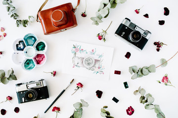 Flat lay. Artist workspace with vintage retro photo camera, and watercolor painted camera, red roses and eucalyptus. Top view arrangement