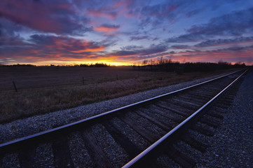 Train tracks and a dramatic colourful sky at sunset;Millet alberta canada