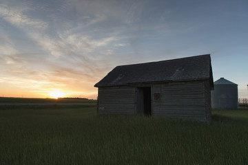A metal silo and wooden shed in a field at sunset;Manitoba canada