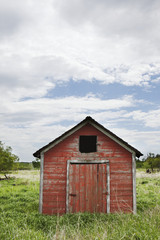 Dilapidated red shed with blue sky and cloud;Manitoba canada