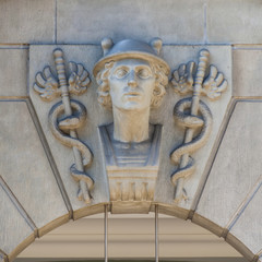 Carved symbol of snakes sceptres and a head above a doorway;Zurich switzerland