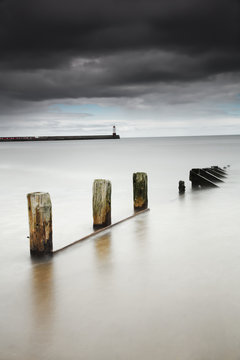 Wooden posts in the tranquil water;Berwick northumberland england