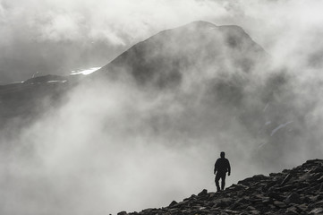 A man walks out of the clouds from the summit of Maol Chean-dearg; Torridon, Scotland