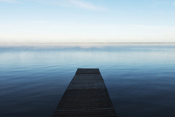 A wooden dock leading out to a misty tranquil lake in Riding Mountain National Park; Wasagaming, Manitoba, Canada